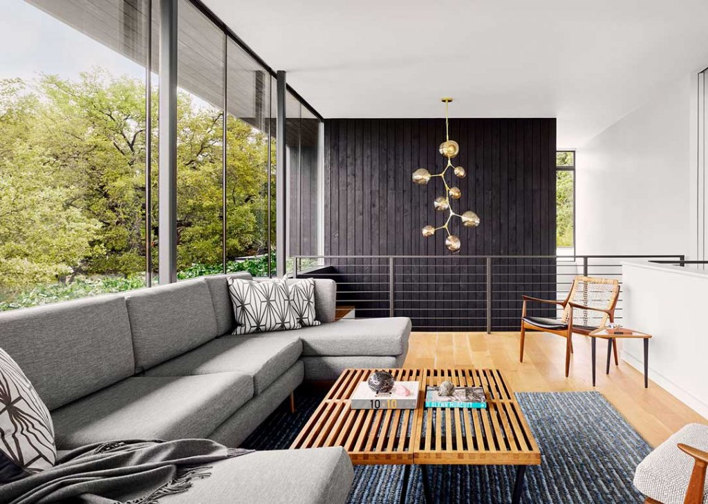 Living room with Shou-sugi-ban wall: Treetops House Austin Texas by Specht Architects Modern Home Photo
